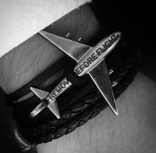brazalete negro con avión platino - remove before flight®