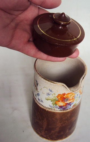 bule antigo ou leiteira em louça marrom com flores coloridas