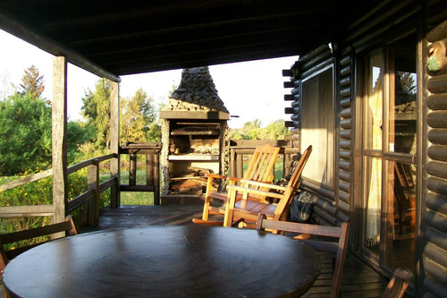 cabaña rústica de troncos frente al río