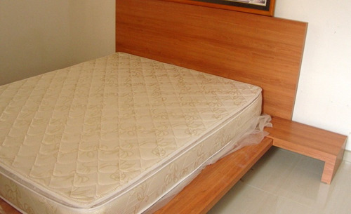 cama tamaño queen con una mesita
