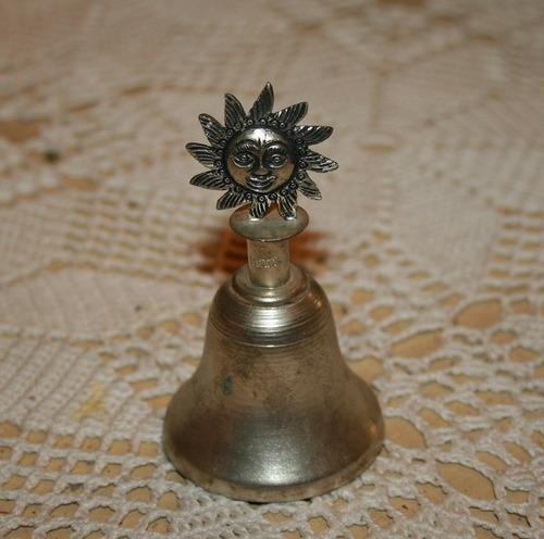 campana de bronce con diseño de sol.