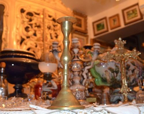 candelabro de bronce antiguo con base redonda.