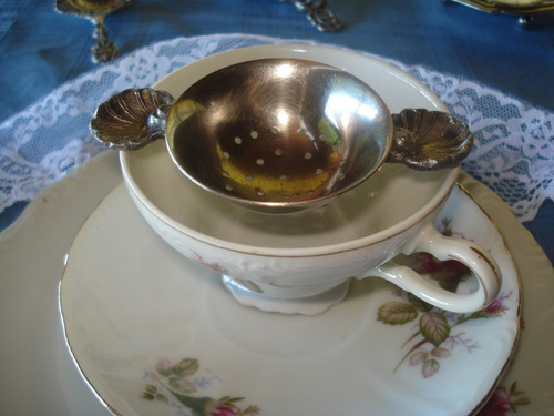 colador de té bañado en plata con asas y patitas