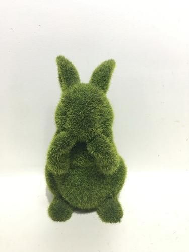 conejo decorativo sentado en pasto sintetico