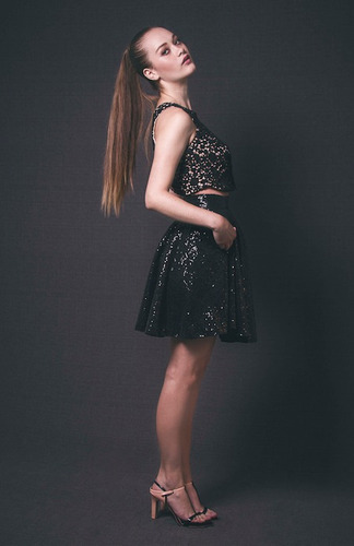falda corta de lentejuelas negra, con bolsillos.
