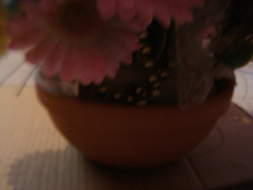 flores artificiales con adornos varios y su envase arcilla