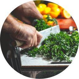 Foto de uma mão cortando verduras