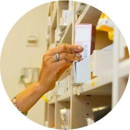 Foto de uma mão retirando uma caixa de remédio de uma prateleira
