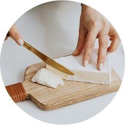 Imagen de una persona cortando quesos.