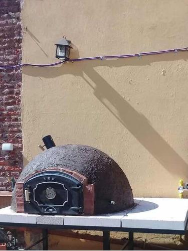 horno de barro con base de hierro y apoyo lateral leña y gas