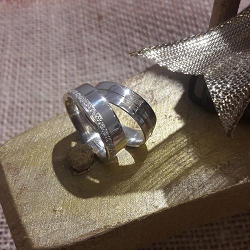 par de alianças de prata cravejada de pedras
