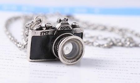 preciosa cadena con dije de cámara fotográfica.