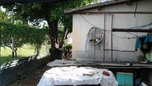 vende lote con casa prefabricada con un tinglado en el fondo