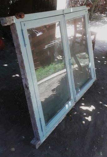 ventana dos hojas de madera con postigon y reja